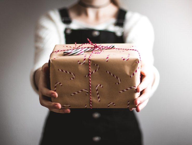 Chica sujeta paquete de regalo con bastones de caramelo en el envoltorio para representar el concepto actividades de Navidad en Alzamora
